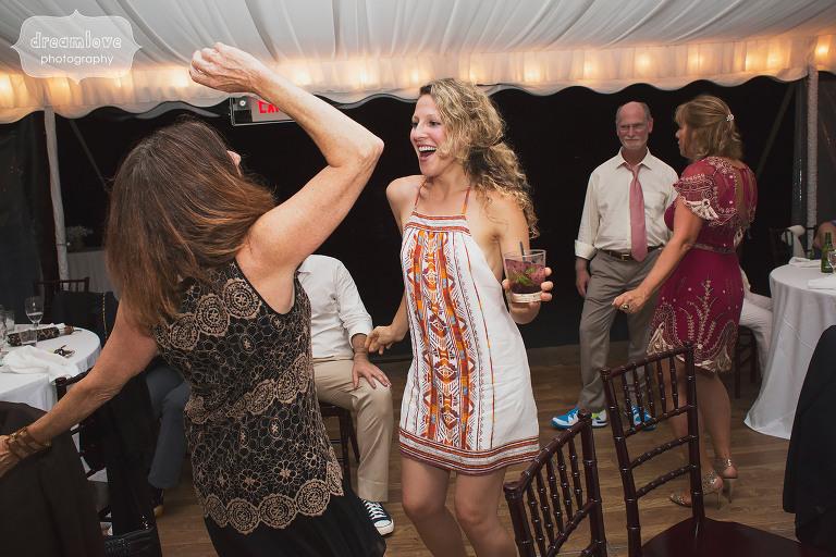 A wedding guest dances in her bohemian wedding dress in Stowe, VT.
