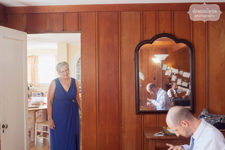Documentary wedding photo of the mother of the groom watching her son.