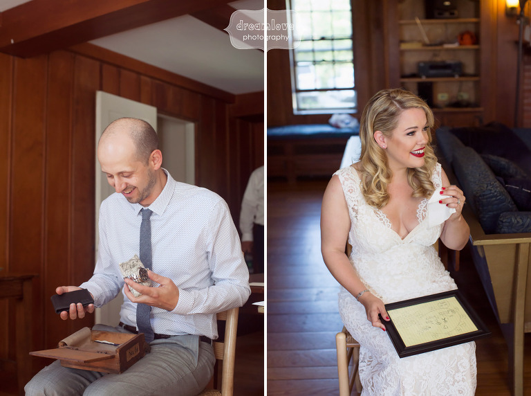 Candid wedding photo of the bride and groom opening their gifts from each other.