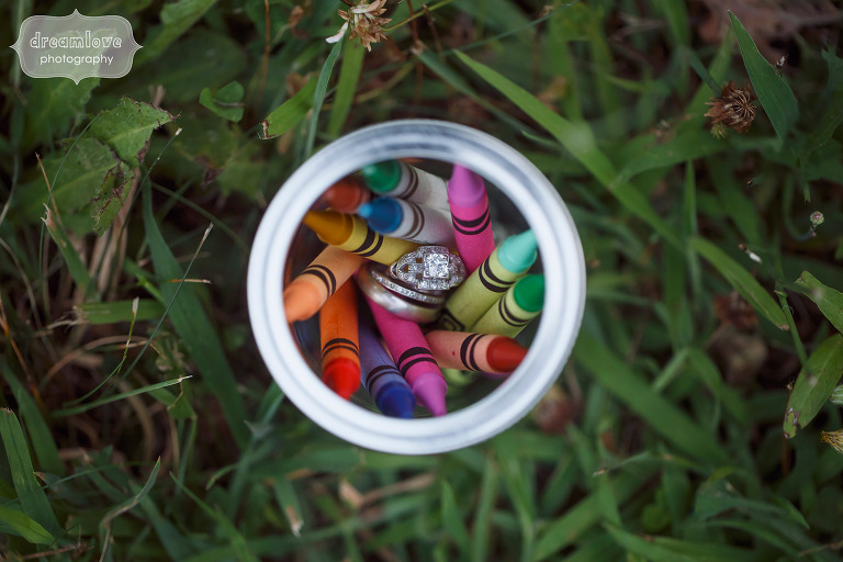 Unique and colorful wedding photo of the wedding rings in a mason jar of crayons.