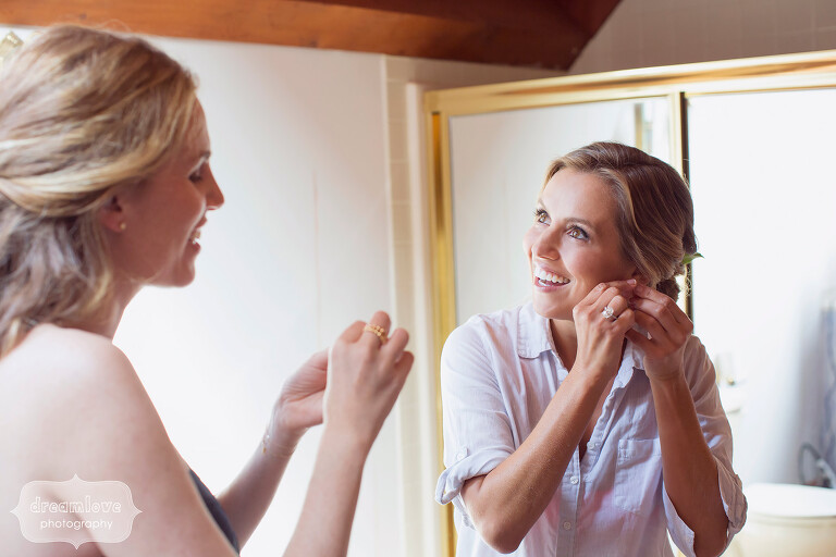 Bride putting earring on before her Cape Cod wedding.
