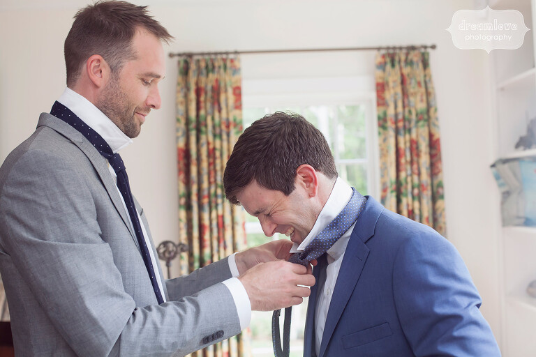 Groom laughs while putting tie on before his wedding on Cape Cod.