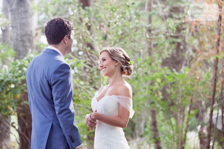 Bride looks shyly at groom on Cape Cod.