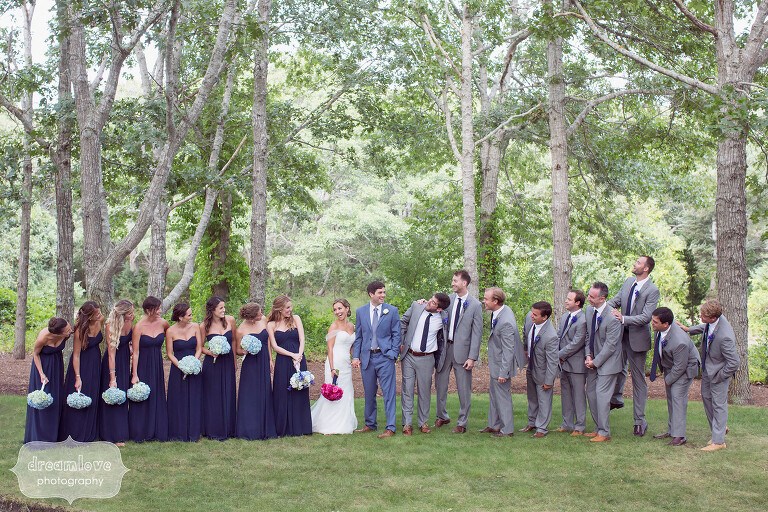 Large wedding party poses in the woods before Cape Cod wedding.