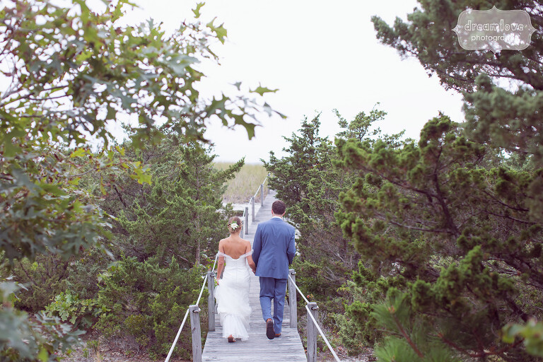 Wedding portrait of bride and groom on boardwalk to beach on Cape Cod.