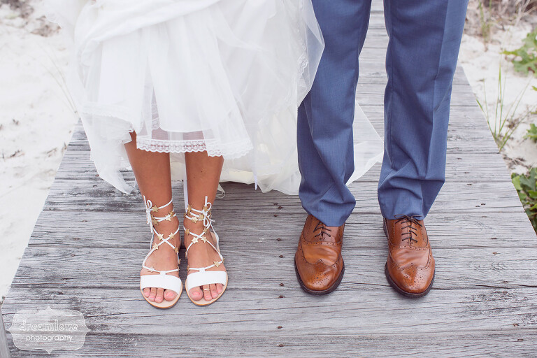 Quirky wedding photo of the bride and groom's feet on an old wooden boardwalk on Cape Cod.