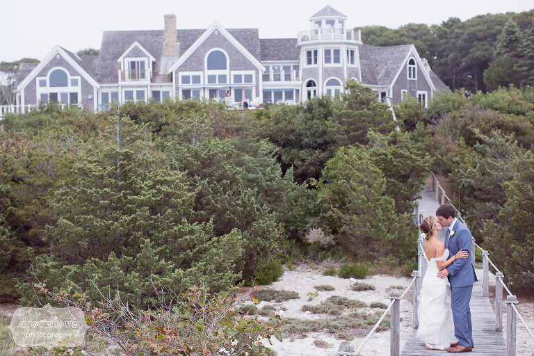 Bride and groom kissing on the boardwalk in front of a mansion on Great Island in West Yarmouth, MA.
