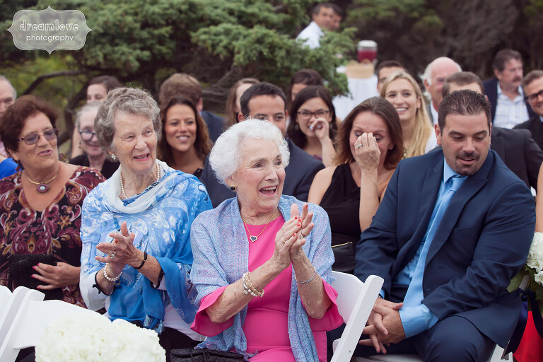 Grandmother clapping as bride walks down aisle during Cape Cod wedding.