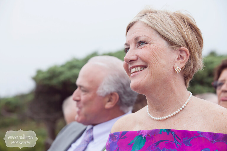 Candid wedding photo of the groom's mother watching the beach ceremony on the Cape.
