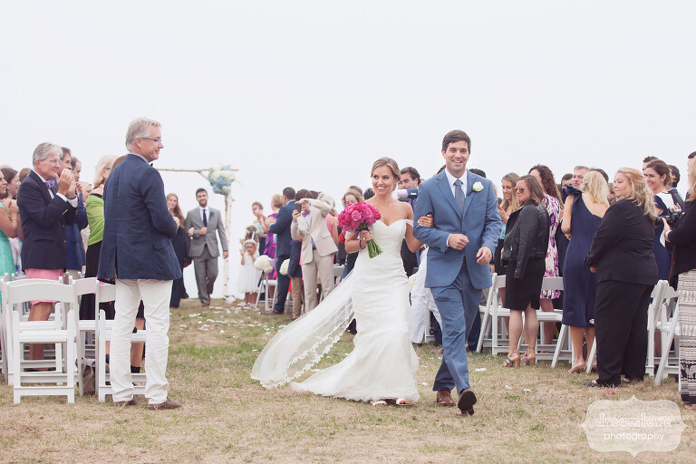Happy bride and groom exit their ceremony at this lighthouse wedding on Cape Cod.