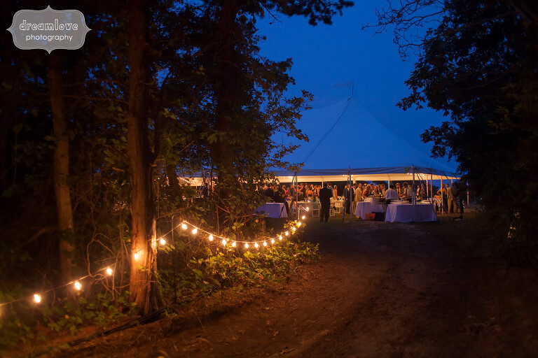 Romantic reception tent walk with cafe lights to Cape Cod wedding.