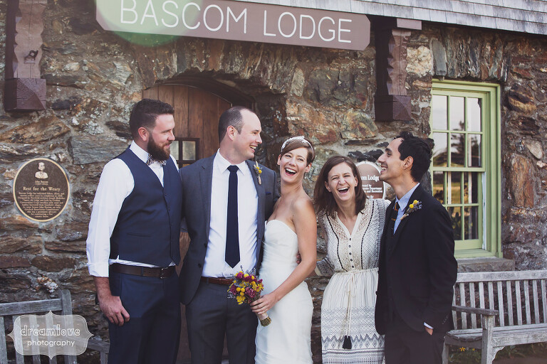Wedding party laughing on the patio in front of the Bascom Lodge in MA.