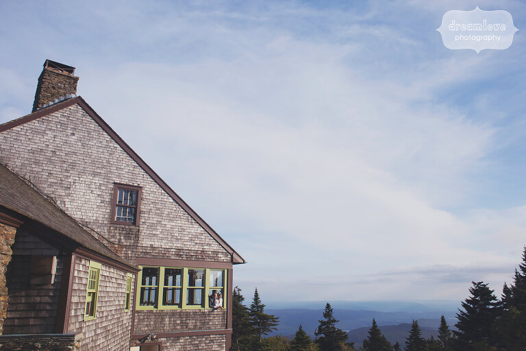 Bride and groom look out the lodge window at this Berkshires wedding venue in western MA.