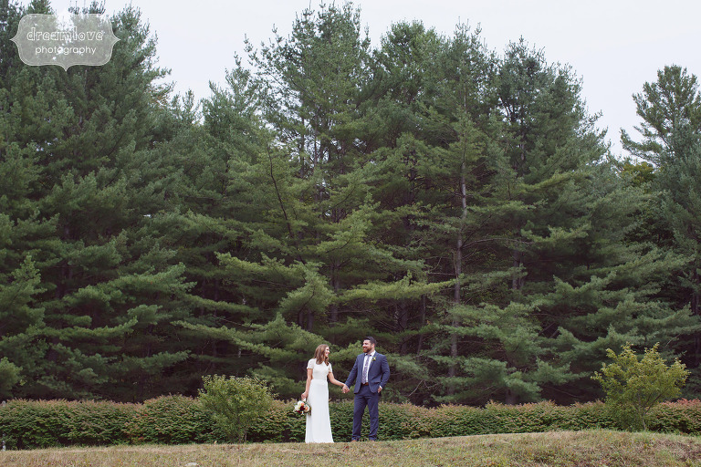 Bride and groom with the forest behind them at this Quechee, VT farm wedding.