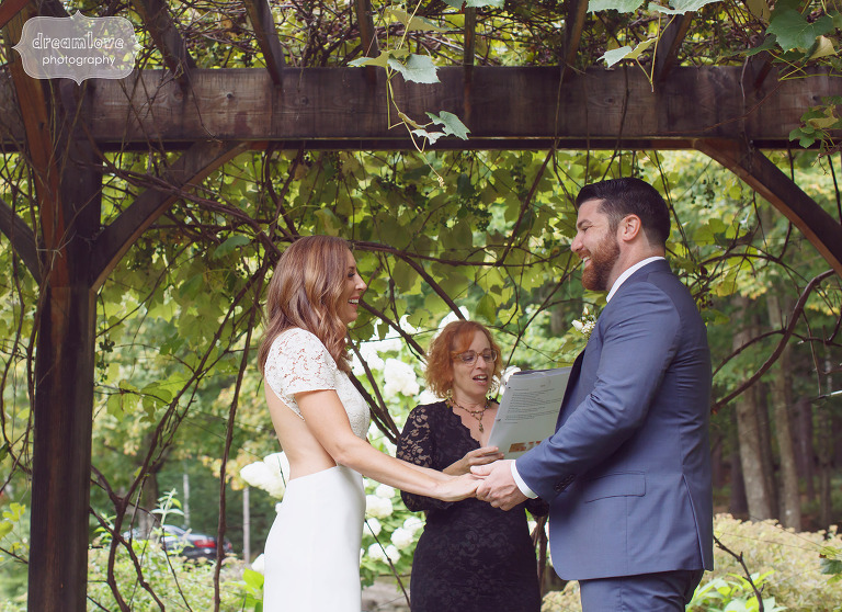 Bride and groom hold hands under an arbor during their outdoor wedding ceremony at the Curtis Hollow Farm.