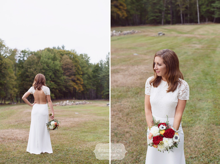 The bride poses in a simple backless wedding dress in the field at the Curtis Hollow Farm in VT.