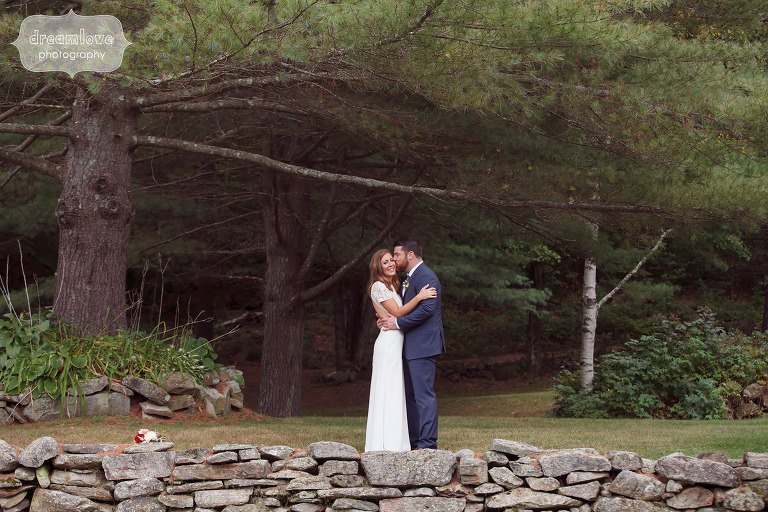 The bride and groom stand behind a stone wall before their Quechee VT wedding at the Curtis Hollow Farm.