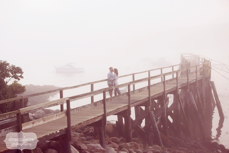 Coastal engagement photo of couple on the pier with ocean landscape in Manchester-by-the-Sea.