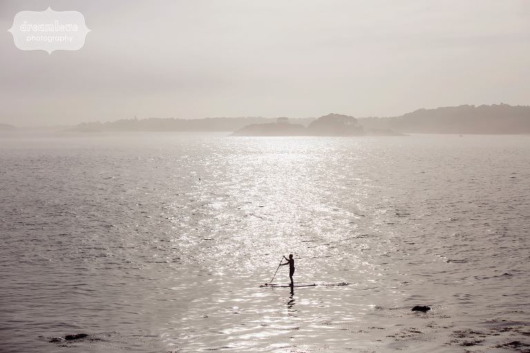 Foggy ocean landscape with SUP boarder during engagement shoot.