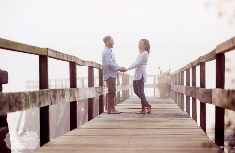 Candid wedding photo of couple holding hands on the pier in Manchester-by-the-Sea.