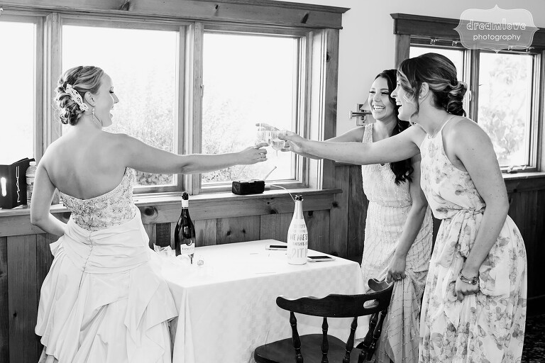 Fine art style wedding photo of the bride doing a toast with her bridesmaids at the Warfield House Inn.