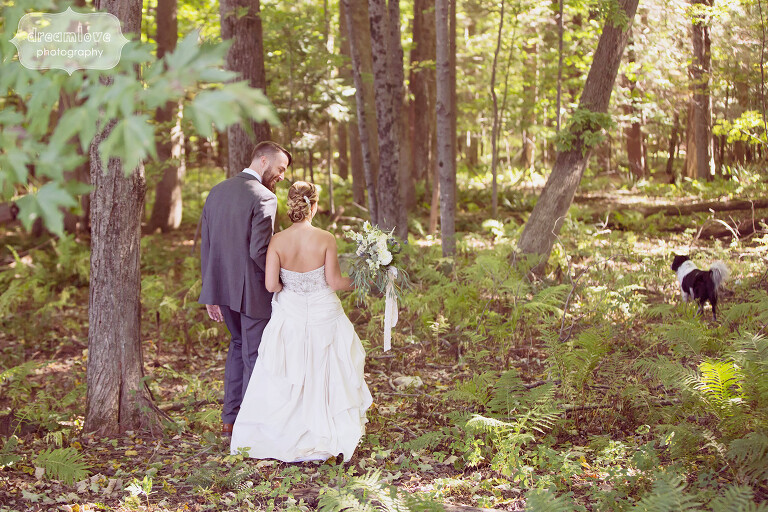 Bride and groom walk through the woods at their wedding in the Berkshires, MA.