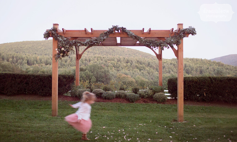 Magical photo of the flower girl running under the wedding arbor at dusk at this outdoor wedding.