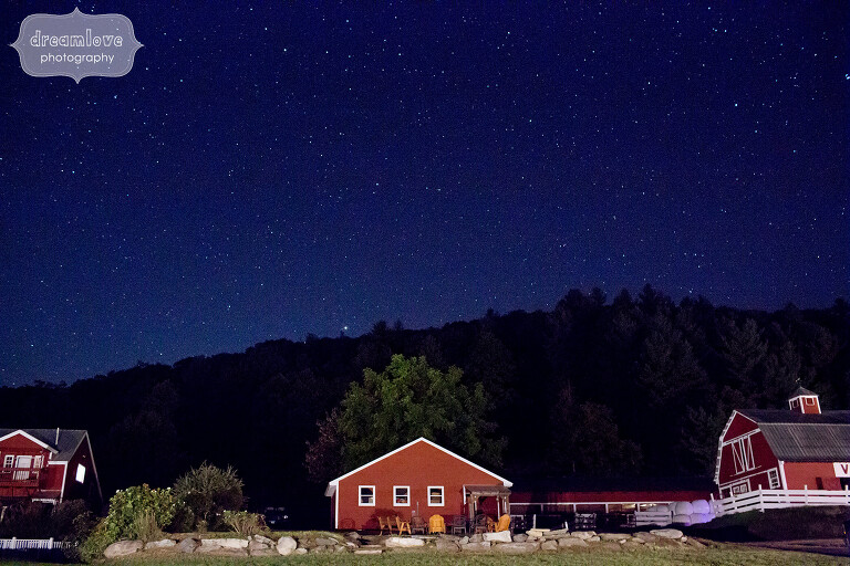 View of the Warfield House Inn venue with a starry blue sky above red barns at twilight.