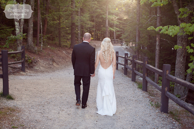 Bride and groom walk away on a woodsy path at Cathedral Ledge.
