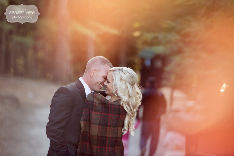 Romantic photo of the bride and groom in a forest wrapped in a plaid blanket.