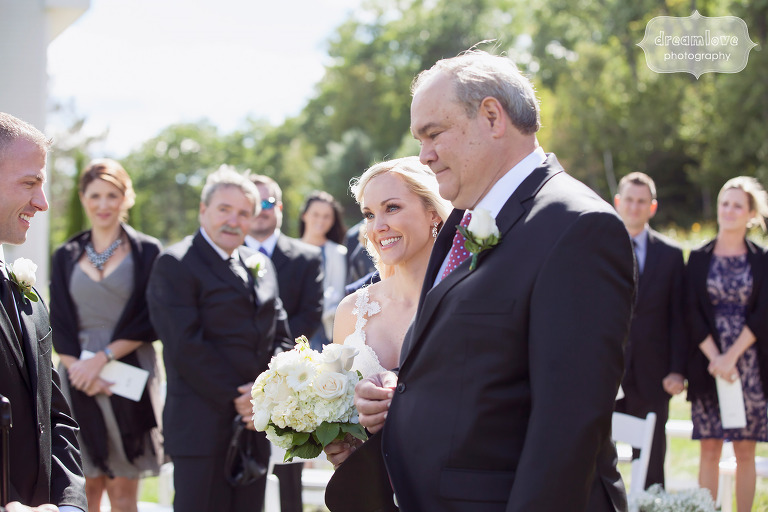 Bride and her father walk down the aisle during this outdoor September wedding ceremony at the White Mountain Hotel.