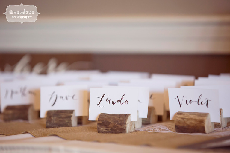 Simple rustic escort cards table set up at this White mountain hotel wedding in Conway, NH using small wooden logs.