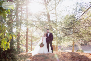 Anthropologie style wedding portrait of bride and groom standing on rocks at the Pavilion on Crystal Lake venue in CT.