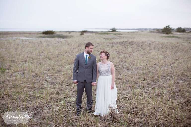 Natural wychmere wedding on cape cod with colorful handmade details bride and groom stand on merkel beach next to the wychmere wedding venue on cape cod junglespirit Choice Image