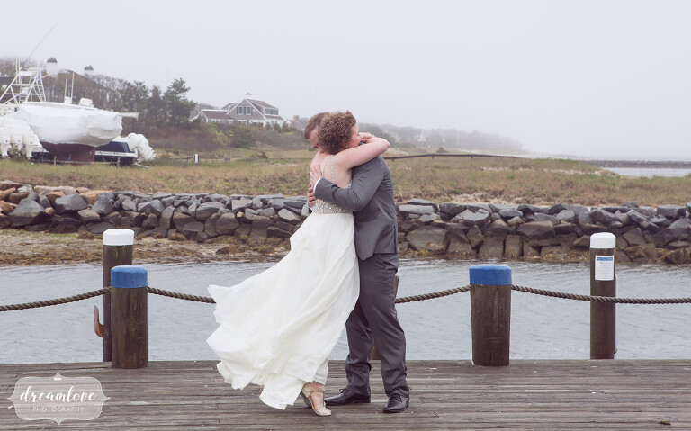 The bride and groom hug each other on the dock in Harwich, MA on the Cape before their rustic beach wedding.
