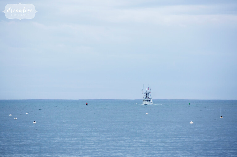 View of an old fishing boat on the ocean at the Wychmere Beach Club venue on Cape Cod.