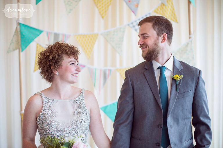 Natural and candid wedding picture of bride and groom with colorful pennants behind them at their Wychmere Cape Cod wedding.