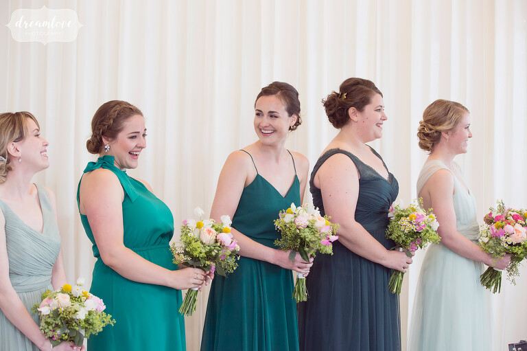 Beach wedding with bridesmaids in various shades of green dresses.