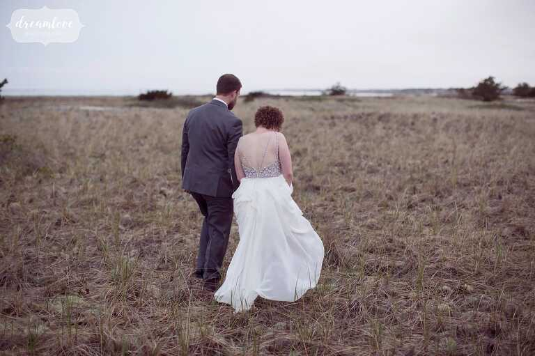 Romantic and ethereal wedding photography of the bride and groom walking onto the beach in Harwich, MA.