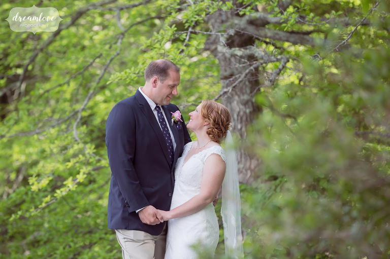 The bride and groom are surrounded by green trees at this NH summer camp wedding on Squam Lake.
