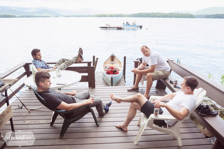 Groomsmen hang out on a dock over Squam Lake before this summer camp wedding begins.