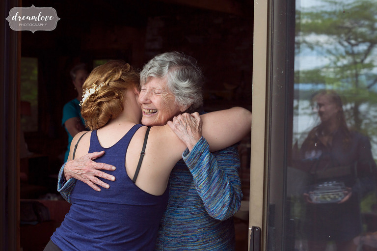 Great photo of the bride and her grandma hugging while getting ready for this summer camp wedding on the lake in NH.
