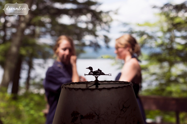 Artistic photo of the bridesmaids with a loon detail while standing next to Squam Lake.