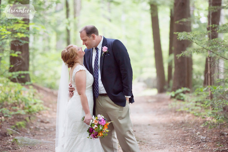 The bride and groom pose for a portrait on a woodsy path at Camp Deerwood.