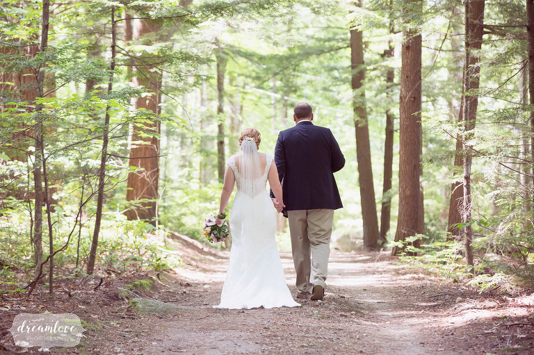 Natural wedding photo of the bride and groom walking down a path before their summer camp wedding on Squam Lake.