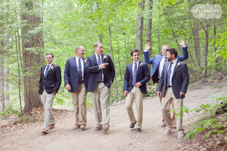 Funny photo of groomsmen walking in the woods before this rustic summer camp wedding in NH.