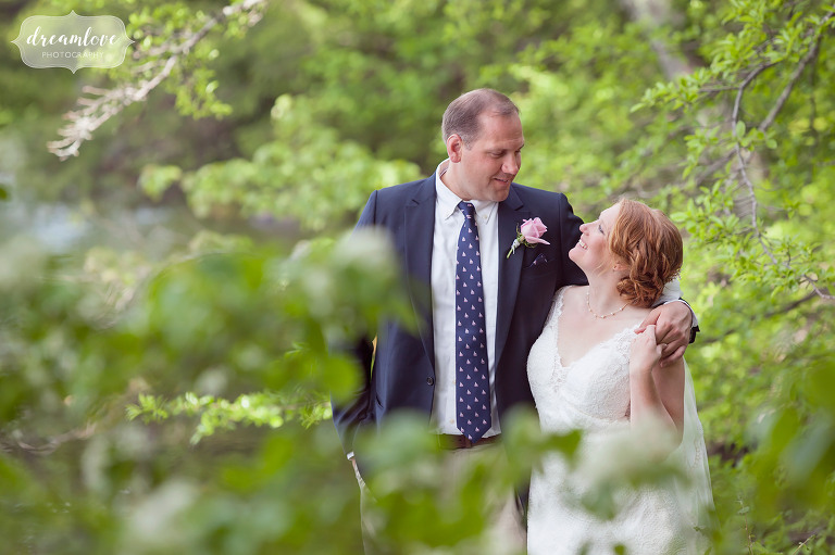 Bride and groom in the woods at their summer camp wedding in New England.