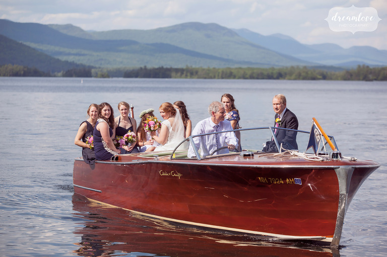 Summer camp wedding party arrives by wooden boat to summer camp wedding in NH.