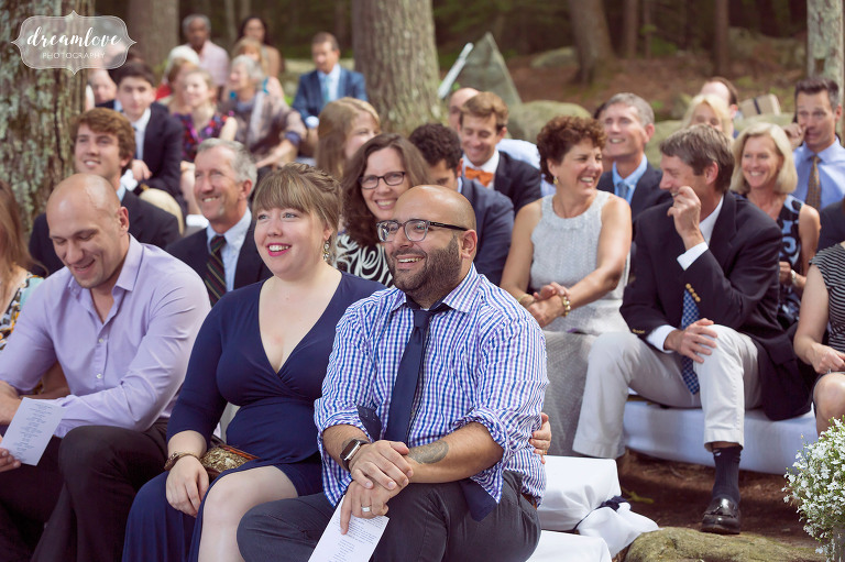 Guests are seated in outdoor amphitheater for this NH camp wedding overlooking the lake.