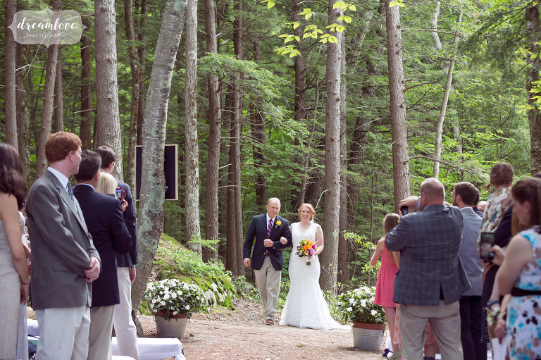 The bride and her father enter the outdoor woodsy cathedral ceremony location at this summer camp in NH.